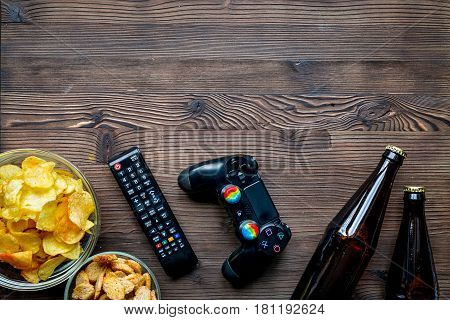 playing console games concept with chips, beer and joypad on wooden table background top view mock up