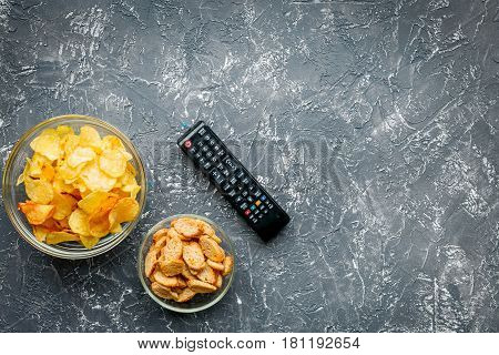 watching movies set with chips and remote control on dark background top view mock up