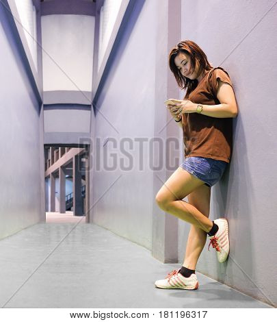 Girl use smartphone while relax from exercise with perspective background