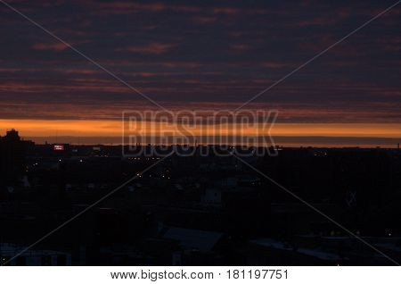 vivid sunset red and orange glow on clouds and dark silhouette of city