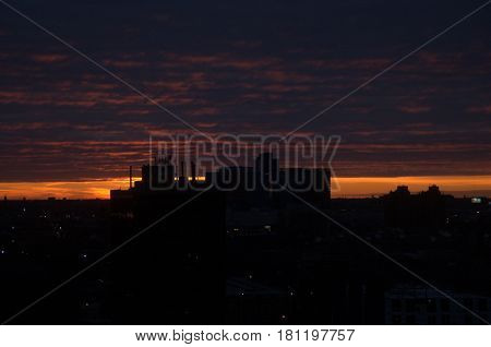 pink clouds at night with dark silhouette of skyline