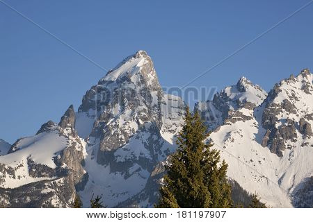 A close up telephoto view of snow-capped Grand Teton peaks