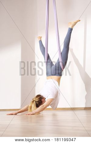 A woman is practicing yoga on a hose, aerial yoga Meditation. Woman meditating in the position of an inverted lotus flower