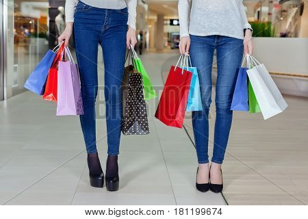 Two Cute Girl Walks In The Mall With Gift Bags. Close Up Only Legs