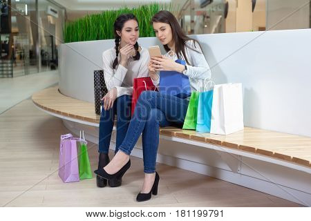 Two Cute Girls Are Sitting On A Bench In The Mall With Gift Bags.