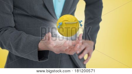 Digital composite of Close up of woman's hand with emoji and flare against yellow background