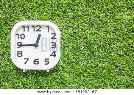 Closeup white clock for decorate show a quarter to one o'clock or 12:45 p.m. on green artificial grass floor textured background with copy space