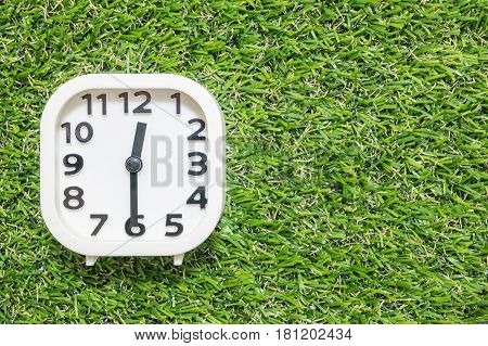 Closeup white clock for decorate show a half past twelve or 12:30 p.m. on green artificial grass floor textured background with copy space