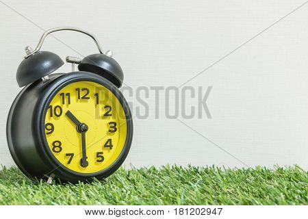 Closeup black and yellow alarm clock for decorate show half past ten o'clock or 10:30 a.m. on green artificial grass floor and cream wallpaper textured background with copy space