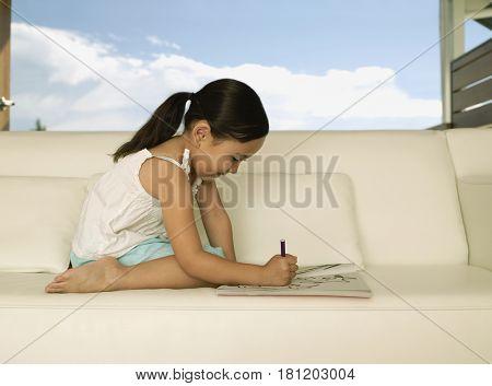 Eurasian girl coloring on sofa