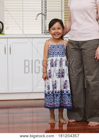 Mixed Race girl standing next to mother