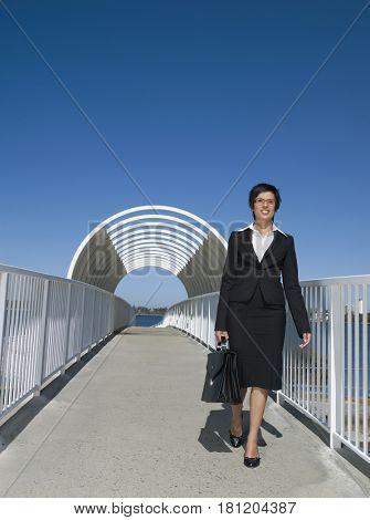 Mixed Race businesswoman walking on walkway