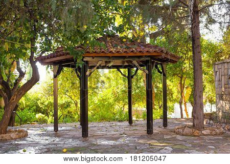 Small Outdoor wooden gazebo with summer landscape background.
