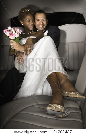 Multi-ethnic newlyweds in back of limousine