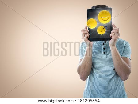 Digital composite of Man tablet over face showing emojis with flares against cream background