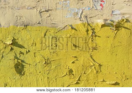 Abstract background of old obsolete yellow wall covered with torn paper