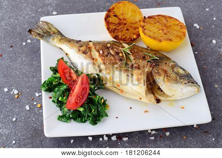 Grilled dorado with grilled lemov, spinach and tomato on a white plate on a grey abstract background. Healthy eating concept. Mediteranean lifestyle