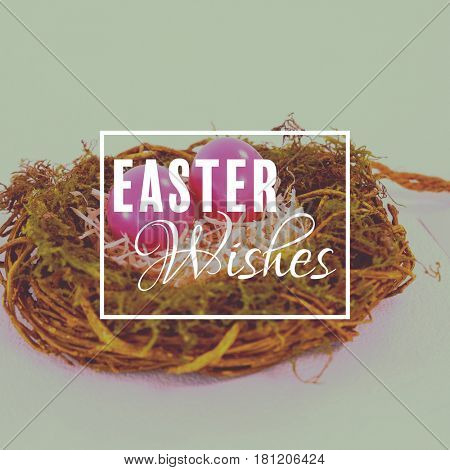 Easter greeting against pink easter eggs in the nest