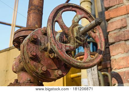 Closeup obsolete weathered red gate valve connection