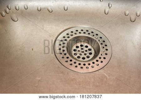 Close-up of stainless steel drain of kitchen sink with strain