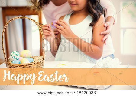 Happy mother and daughter painting easter eggs against happy easter logo