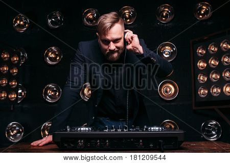 Young disk jockey with headphones and mixer checking equipment. Bearded professional DJ prepare to play famous music at nightclub dance party.