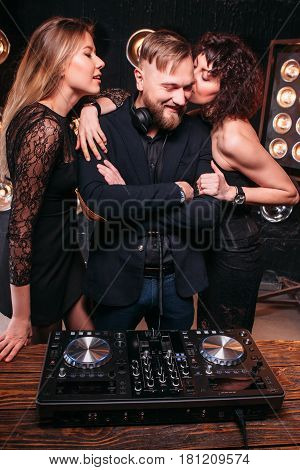 Two beautiful sexy girls flirt with handsome bearded disk jockey at nightclub party. Nightlife, music, lifestyle, playful clubbing people relax.