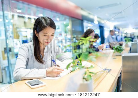 Woman study on the note with her cellphone in university