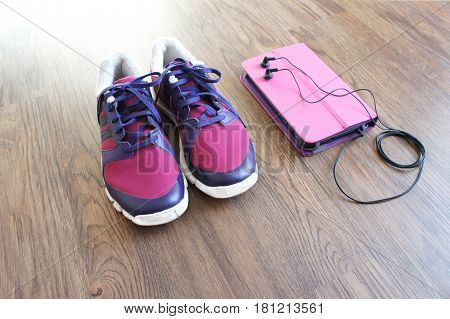 pink sneakers and a tablet in a pink case with headphones on wooden background