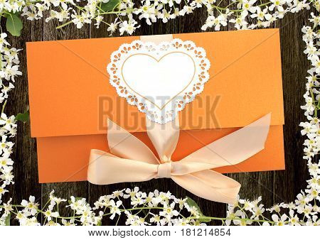 gift envelope tied with a pink ribbon on dark wooden background with flowers of cherry