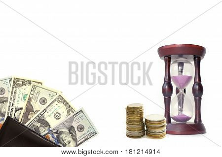 Hourglass, two stacks of coins and dollars on white background. Concept on the topic of Finance and time.