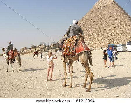 GIZA, EGYPT - MAY 2, 2015: A man on a camel and tourists at the great pyramid of Cheops in Egypt