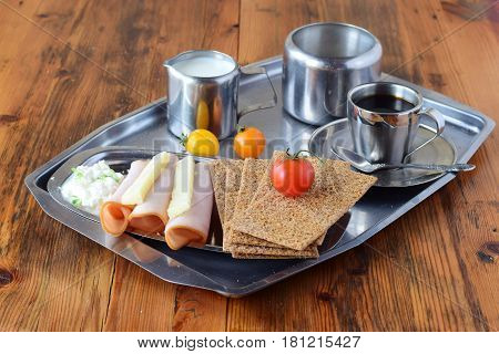 Metal tray with crispbread, cheese, cottage cheese, ham, cherry tomato, cup of coffee, sugar jar, creme jar on a wooden background. Healthy breakfast. Healthy eating
