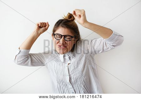 Dancing crazy girl in specturales and white striped shirt holding hands up with funny emotion on her face. Young woman listen favourite music and having positive feelings. Humorous facial expression