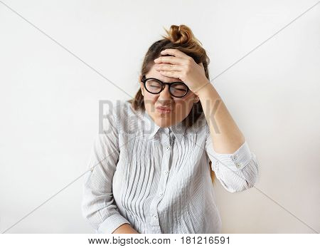 Stress at work concept. Portrait of funny young female office worker in striped shirt and glasses having headache holding her hand to the head. Beautiful young female feeling sick and strong migraine