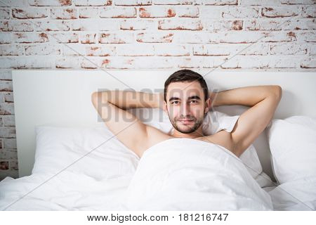 Handsome Well Built Man Resting In His Bed On Brick Wall In Room At Home