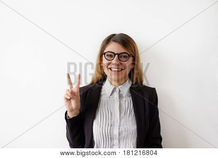 Headshot of a cheerful happy female student in formal outfit showing victory sign and looking at camera isolated on the white background. Pretty girl looking at the camera posing with peace gesture