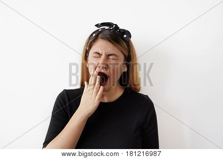 Portrait of tired sleepy businesswoman yawning, working in the office. Fashionable female student posing in the studio wants to sleep after hard day. Overwork and sleep deprivation concept