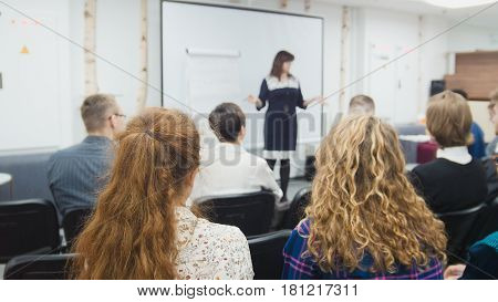 Business woman - speaker at seminar - performing female teaching at international conference, de-focused shot, close up