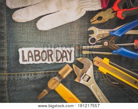 Labor day background concept - Jeans many handy tools with labor day text on Jeans background top view