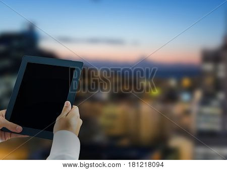 Digital composite of Hands with tablet in the city at nigth