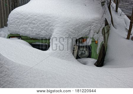 A plentiful nighttime snowfall covered the car completely.
