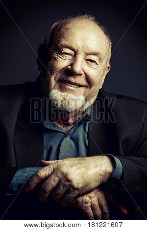 Portrait of a smiling old man over black background. Old age concept.