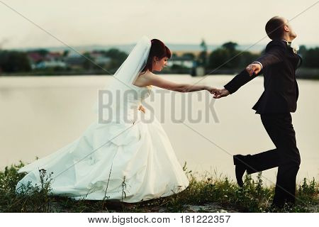 Groom Runs Along The Lake's Shore Holding Bride's Hand Tightly