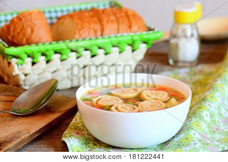Diet soup with vegetable mix and fried omelet in a bowl. Bread slices, spoon on a rustic wooden background. Healthy soup with omelet, carrot, peas, leek, cauliflower and potatoes