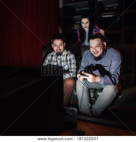 Two young guys with joysticks play video game on couch at home, in dark room. Concentrated girl watch competition.