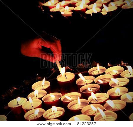 hands of an elderly woman who lights a candle during the Holy Mass in the Christian church and many lit candles