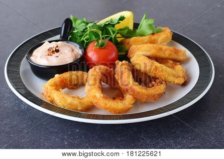 Calamary rings fried with spicy souce and rocca. Mediterranean lifestyle. Healthy food.