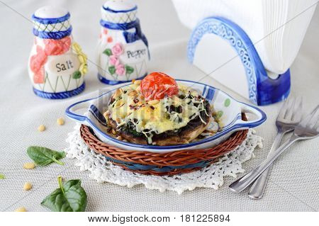 Grilled portobello mushroom with spinach, pinenuts, onions and cheese in a ceramic pot. Helathy eating concept. Mediterranean lifestyle