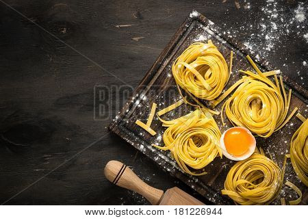 Fresh italian raw homemade pasta tagliatelle at wooden table. Italian food background. Top view copy space.